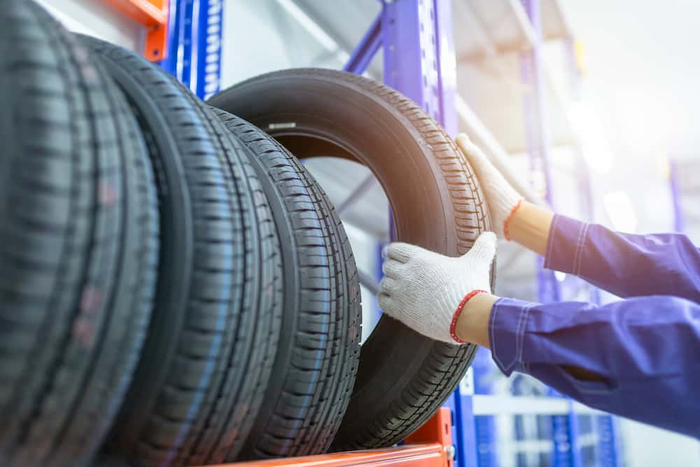 engineer removing a tyre from a rack